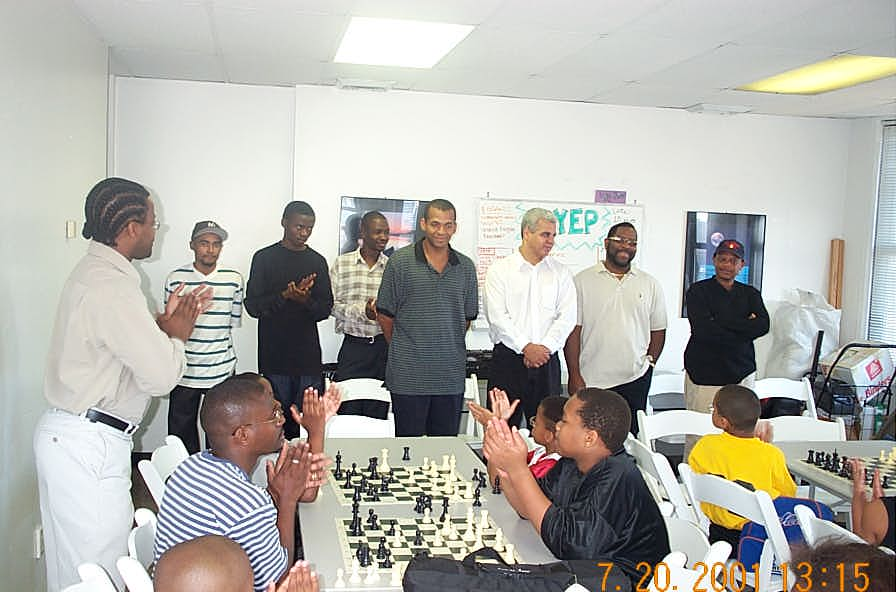 GM Maurice Ashley (standing left) introduces Wilbert Paige participants to Harlem Chess Center students. The players are: (L-R) FM Kenny Solomon, IM Amon Simutowe, NM Grace Nsubuga, FM Stephen Muhammad, NM Ernest Colding, NM Norman Rogers, and IM Watu Kobese. Copyright © 2001, Daaim Shabazz.