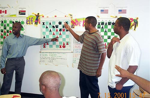 "NM Jerald Times analyzes position with FM Stephen Muhammad at the Wilbert Paige Memorial tournament in July 2001. FM William ""The Exterminator"" Morrison looks on with the rest of the audience. Copyright © 2001, Daaim Shabazz."