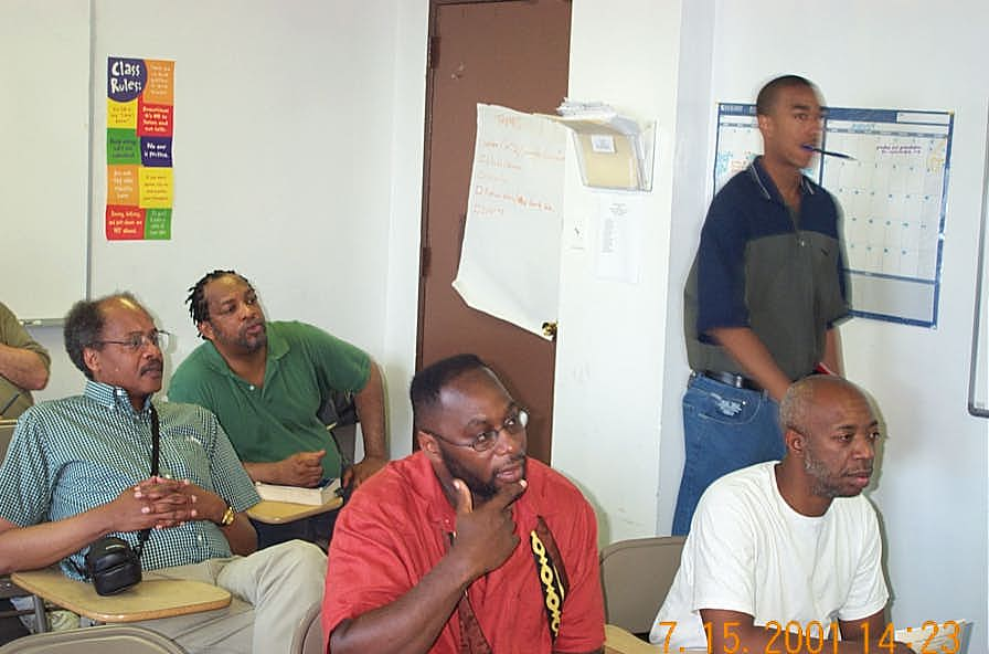 Onlookers in the analysis room including Willie 'Pop' Johnson (back), NMs Frank Street (blue checkered shirt) and Glenn Bady (red-orange shirt).  Copyright ©, Daaim Shabazz.