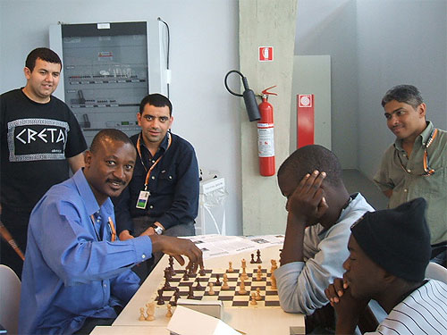IM Odion Aikhoje blitzing with Zambia's Chitumbo Mwali at 2006 Olympiad. Jamaica's Shane Matthews is standing on the right.