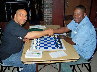 Eddie Mark III (right) shake hands with Douglas DuBose prior to the final round of the Buffalo City Championship. The game was quickly drawn giving Mark the title. Photo from buffalochess.blogspot.com.