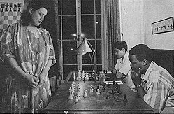 Above is K.K. Karanja (seated) playing GM Maya Chiburdanidze in a simultaneous exhibition at the Marshall Chess Club in 1987. At the time, Maya was the Women's World Champion.  Photograph by Nigel Eddis.