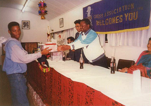 Pedro receives his prize for winning the 1993 Africa Junior Chess Championship from the late Chairman of Kenya Chess Association Fred Sagwe while Vice-Chairman Francis Rodrigues looks on. The event was held at the YMCA in Nairobi, Kenya and ran from 11th to 26th December 1993. Photo credit Kim Bhari.