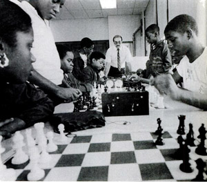 Plotting moves, the Bad Bishops are closely watched by their coach, Jeffrey Chesin (at end of table). Kevin Giles and Michael Allen  play a game of blitz (center).