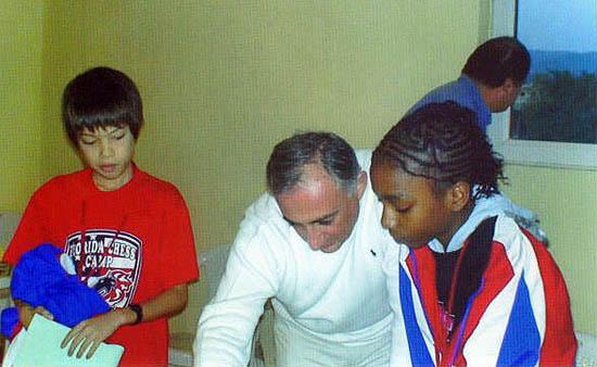 Darrian getting help from coach Armen Ambartsoumian while Ray Robson looks on. GM John Federowicz checks the Batumi scenery.