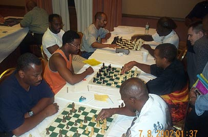 FM Stephen Muhammad (right center) showing GM Maurice Ashley his game against IM Eugene Perelshteyn. Both Muhammad and Ashley have qualified for the 2003 U.S. Championship.