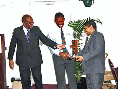 NM Shane Matthews (right) accepts his first place trophy from JCF President Ian Wilkinson (left) and National Master Geoffrey Byfield (center).