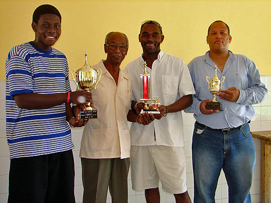 Elton Joseph (far left) being presented his Heroes Cup while Tameko McDonald and Donovan Williamson flash their trophies. Dr. Harold Munnings (2nd from left)  sponsored the tournament. Photo by Bahamas Chess Federation.