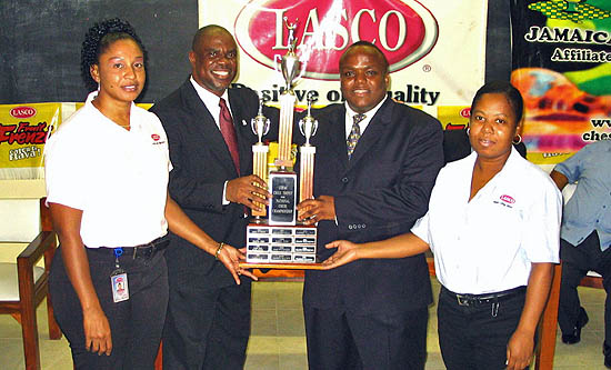 Duane Rowe receives his award from JCF President Ian Wilkinson while Alice Manhertz (left) and Swylen Davy (right) of LASCO Foods look on.