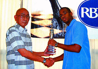 Brandon Wilson (right) is presented with the Shane Matthews Junior Champion Trophy by International Chess Arbiter Serafin Chuit Perez of Cuba. Chuit Perez is in Jamaica conducting International Chess Arbiter seminars. Copyright ©  2006, Daaim Shabazz.