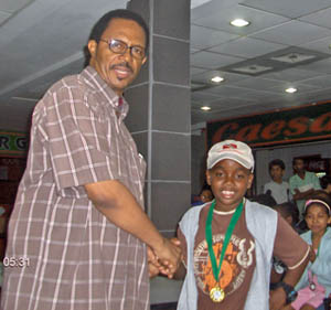 RJ Nelson wearing his medal after wining the under-10 title. Andrew Bowles of the T&T Chess Academy congratulates him.