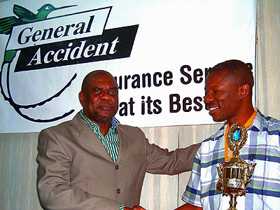 NM Geoffrey Byfield (right) receives the Dr. Harold Chan Trophy from JCF President Ian Wilkinson. Photo by Jamaican Chess Federation.