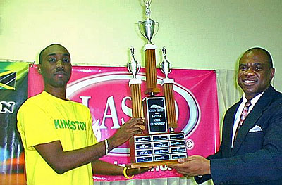 FM Warren Elliott (left) accepts the LASCO National Chess Champion Trophy from JCF President Ian Wilkinson in this file photo. Photo by Jamaican Chess Federation.