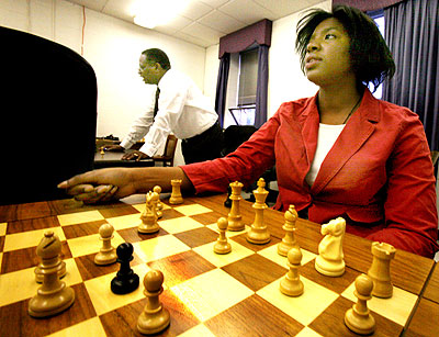 Dr. Sid Credle, center, the dean of Hampton University's business school, uses chess as a way to teach critical thinking. Nneka Uzoh, about strategy. Photo by John H. Sheally II/THE VIRGINIAN-PILOT.