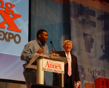 "Orrin Hudson tells the ""Donald Trump story"" in front of 40,000 attendees at the Real Estate and Wealth Expo in Atlanta. Trump seems to be enjoying the rendition. Photo courtesy of BeSomeone, Inc."