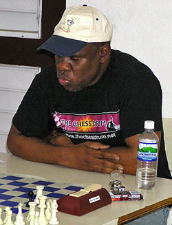 Jamaican Chess Federation President Ian Wilkinson dispatching of rising junior Hakim Buchanan.