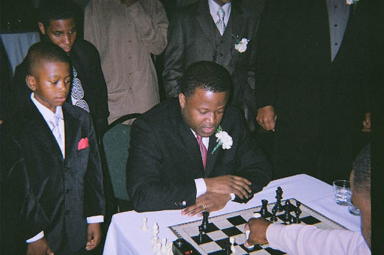 GM Maurice Ashley playing blitz with Kasaun Henry while onlookers take note. Photo by Kevin Fite.