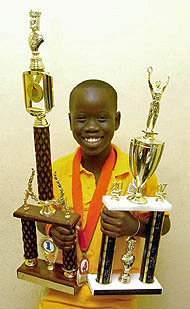 Tewana Mellace showing off his trophies from the 2007 Miami Orange Bowl. Photo by Jamaica Chess Federation.