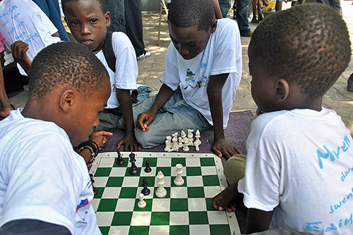 Haitian youth playing with FIDE donated chess equipment.