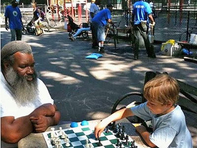 Yacahudah 'Y.A.' Harrison playing chess with a neighborhood child this summer on the table with a chessboard inlay inside Emerson Playground at Inwood Hill Park. (DNAinfo/Carla Zanoni)