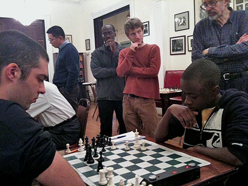 Joshua Colas (right) in action versus NM Leonardo Martinez at the Marshall Chess Club. Guy Colas in background watching. Photo by James Black, Sr.