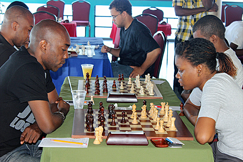 Warren Elliott (front, left) was held to a draw by Deborah Porter (front, right) at the 2012 Jamaica Chess Open, however Elliott defeated the rest of his opponents to claim first place.