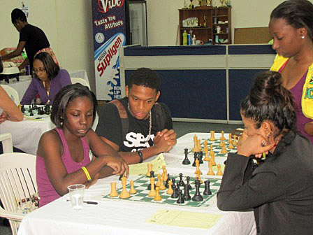 Corine Howard and Adita Soondarsingh analyse their 18-move game with Krishna Gray watching. All three had short draws with the other two.