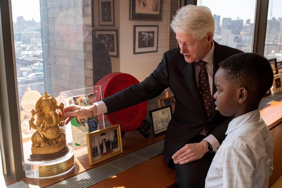 42nd U.S. President Bill Clinton showing Tani a depiction of Ganesh, the Hindu God who is the remover of obstacles. Photo by Nicholas Kristof.