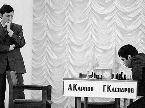 Anatoly Karpov hovers as Garry Kasparov ponders next move in 1984 match.