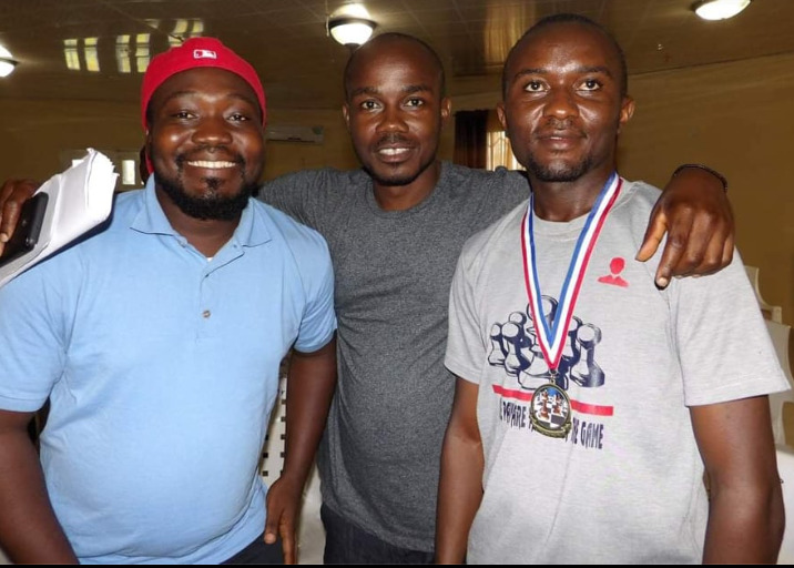 Left to Right: Former Champions James Stephen Tondo III and FM Barcon Harmon with Thomas Saah wearing his championship medal. Photo by Mario Kpan