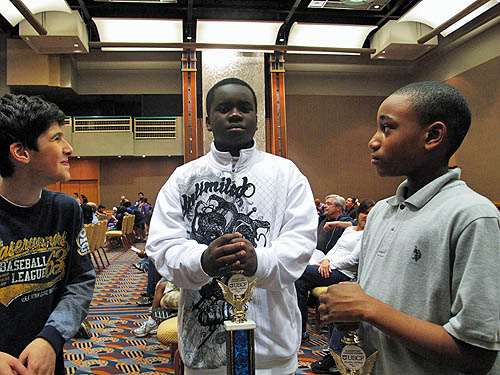 Issac Bareyev (left) and James Black, Jr. (right) enjoy the moment with I.S. 318 teammate, Justus Williams, 2010 National Elementary Champion