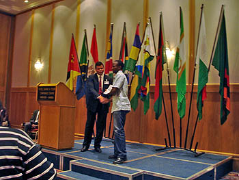 Uganda's Steven Kawuma receiving his participation certificate.