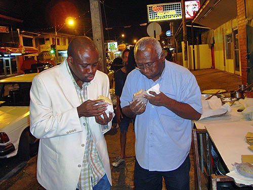 Nigerian IM Oladapo Adu (Left) enjoys a Roti an East Indian culinary delight with Carlyle Singh of the Trinidad and Tobago Chess Foundation.