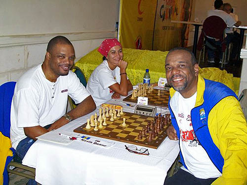 Classic Photo: IM Kevin Denny battles FM Philip Corbin in the last round of the Caribbean Chess Carnival. WGM Ilaha Kadimova of Azerbaijan delights in the moment. Photo by FM Philip Corbin.