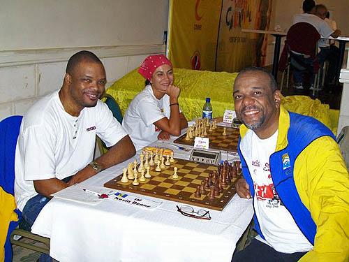 Classic Photo: IM Kevin Denny battles FM Philip Corbin in the last round of the Caribbean Chess Carnival. WGM Ilaha Kadimova of Azerbaijan delights in the moment. Photo by FM Philip Corbin.