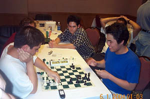 FM Daniel Fernandez and GM Hikaru Nakamura in an impressive show of 1-minute chess. FM Matthew Hoekstra looks on. It was 1:03am. Copyright © 2004, Daaim Shabazz
