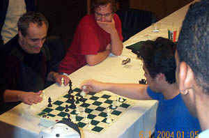 GM Dmitry Gurevich tries Nakamura and swindles the young phenom for a draw. FM Stephen Muhammad (right) looks on. Copyright © 2004, Daaim Shabazz