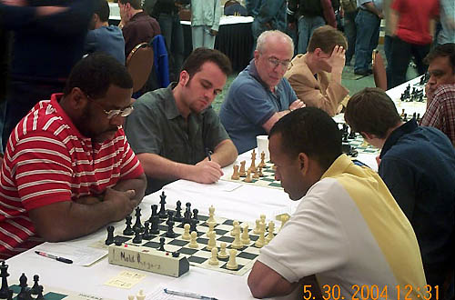FM Norman Rogers and IM-elect Stephen Muhammad face off in 4th round battle. Muhammad won a wild encounter despite of his king getting stuck in the center. Copyright © 2004, Daaim Shabazz
