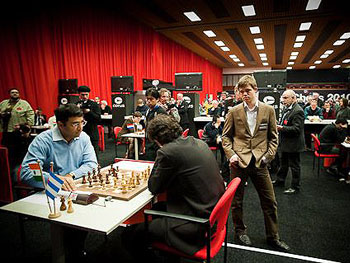 Anand squaring off with Dominguez with Nakamura and Carlsen watching. Photo by Fred Lucas.