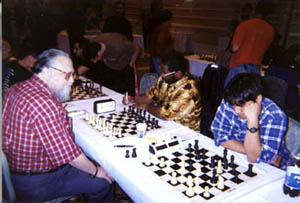 NM Jerry Hanken vs. NM Norman 'Pete' Rogers. On the right 16-year old star, FM Daniel Fernandez ponders his next move. Copyright © 2002, Daaim Shabazz.