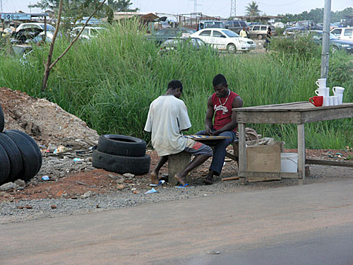 Men playing checkers. Still no sign of chess in Ghana.