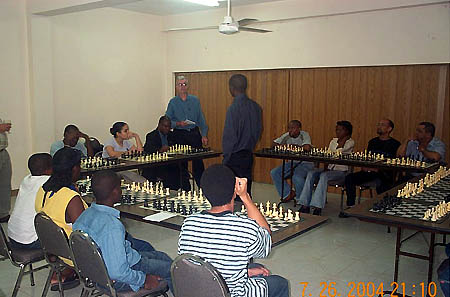 Bob Wheeler gives the participants instructions before the 15-board simultaneous exhibition begins. Jamaican Chess Federation President Ian Wilkinson (facing Simutowe) is at board #1. Copyright © 2004, Daaim Shabazz.