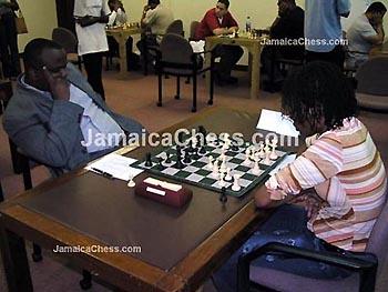 Duane Rowe with a Fischer pose vs. Women's Champion, Deborah Richards. Copyright © 2004, JamaicaChess.com