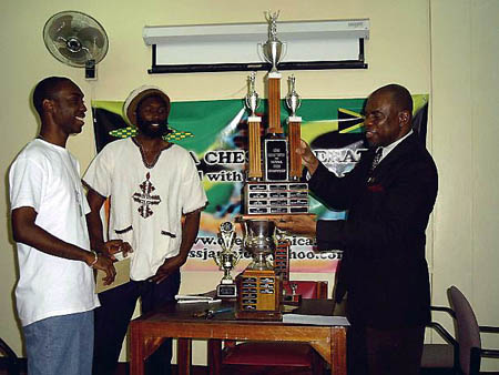 Jamaican President Ian Wilkinson (right) prepares to present FM Warren Elliott (left) with the Championship trophy while Negash Bezaleel looks on. Copyright © 2004, Mark Bowen