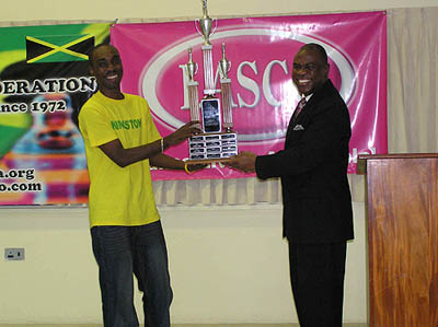 Jamaican Federation President Ian Wilkinson presents championship trophy to FM Warren Elliott as Jamaican National Champion.
