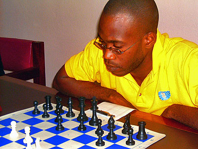 Equitable Brown has closed the gap to a mere ½-point. Warren Elliott, the leader, was upset by Mikhail Solomon. Photo by Jamaica Chess Federation.