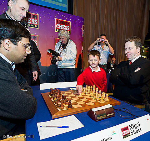 This picture of the boy playing the ceremonial move may be worth something ten years from now. Are we looking at a future English GM? If so, he is in distinguished company includin GM John Nunn in the background. Photo by Ray Morris-Hill.
