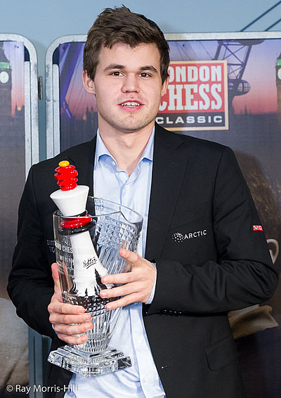 Magnus Carlsen receiving both Grand Chess Tour Cup and London Chess trophy. Photo by Ray Morris-Hill.