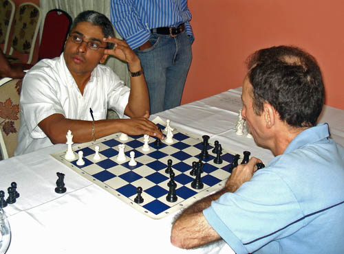 Jamaican National Master Shane Matthews (left) analyses his Round one game with Cuban International Master Jose Vilela.
