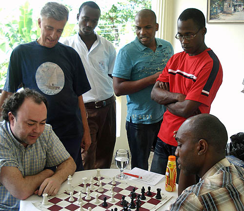 Grandmaster Holmes (seated left) does a post-game analysis with Jamaican FIDE Master Warren Elliott (seated right). Looking on standing from left are Swedish FIDE Master Bengt Hammar, Jamaica's National Junior Chess Champion  Damion Davy of Camperdown High, FIDE Master Jomo Pitterson and Jamaican National Champion Equitable Brown.